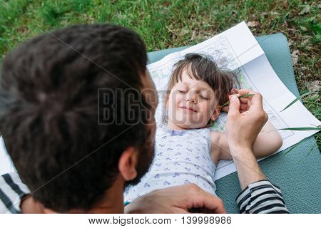 Father tickling daughter with grass, enjoying rest outdoor. Happy family pastime