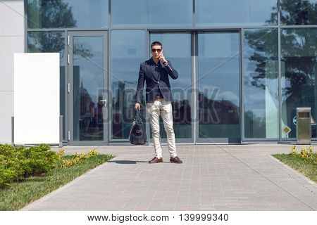 Young official man expert calling via cell telephone while standing outdoors near modern glass building, young male employer talking on mobile phone