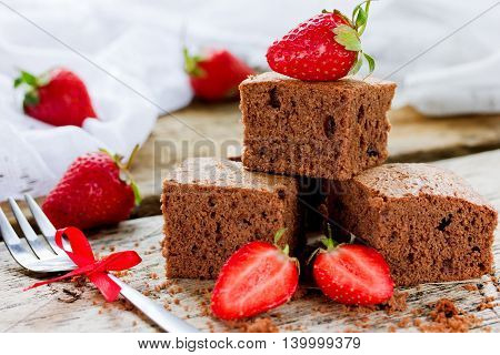 Chocolate cake with strawberry traditional American cuisine dark brownie with chocolate selective focus