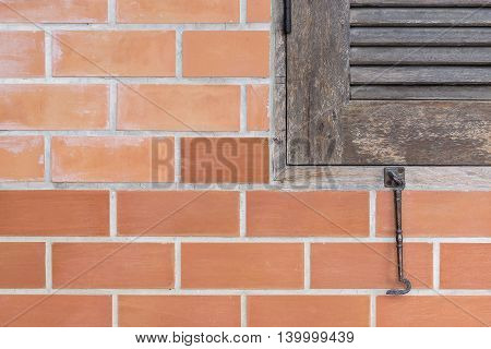 The part of old wooden window with the red brick wall
