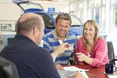 image of car keys  - Couple filling in paperwork in car showroom - JPG