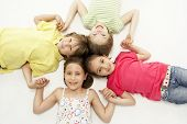 stock photo of holding hands  - Circle of four young friends smiling and holding hands - JPG