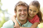stock photo of father daughter  - Portrait Of Father And Daughter In Park - JPG
