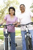 foto of portrait middle-aged man  - Senior Couple Riding Bikes In Park - JPG