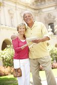 Senior Couple Walking Through City Street With Map