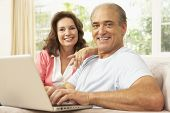 stock photo of mature men  - Senior Couple Using Laptop At Home - JPG