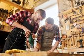 Постер, плакат: profession carpentry woodwork and people concept two carpenters with electric drill drilling woo