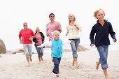 stock photo of extend  - Three Generation Family Running Along Winter Beach Together - JPG
