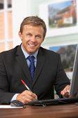foto of real-estate agent  - Male Estate Agent Working At Desk - JPG