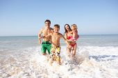 picture of ten years old  - Young family play on beach - JPG