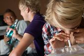 stock photo of underage  - Group Of Teenage Boys And Girls Taking Drugs At Home - JPG
