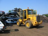 picture of scrap-iron  - a truck lifting a car wreck at a scrapyard in norway - JPG