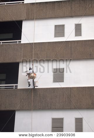 Painter hanging on rope