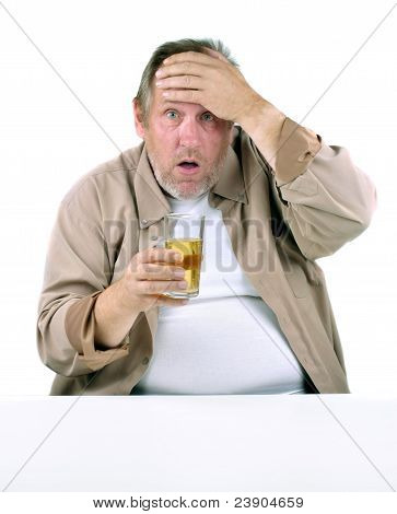 Horrified Man In His 50S Sitting At A Table With A Drink
