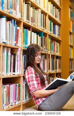 Portrait of a young female student reading a book in a library