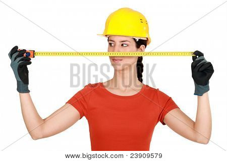 Female builder with a tape measure