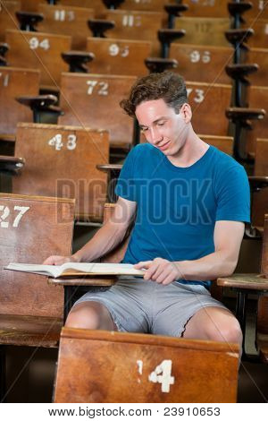 Young studious boy studying at university hall