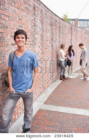 Portrait of a student posing while his friends are talking outside a building