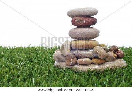a pile of zen stones on the grass on a white background