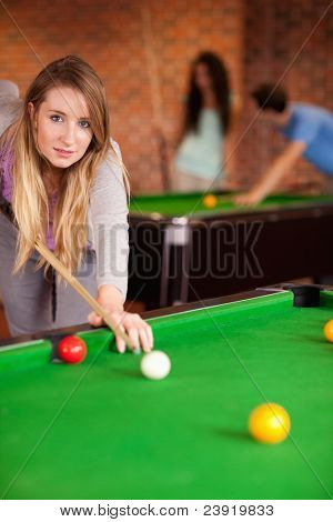 Portrait of a young woman playing snooker in a student home