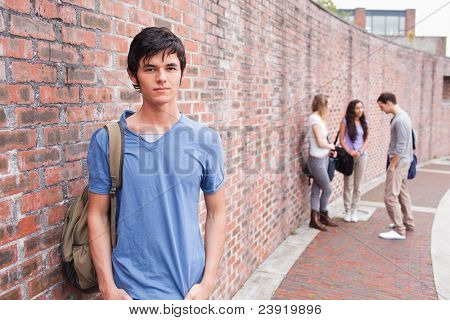 Student posing while his friends are talking outside a building