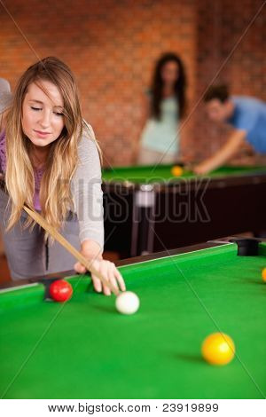 Portrait of a cute woman playing snooker in a home student