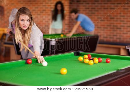Student woman playing snooker in a student home