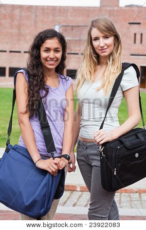 Portrait of smiling female students posing outside a building