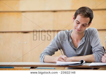 Male student writing notes in an amphitheater