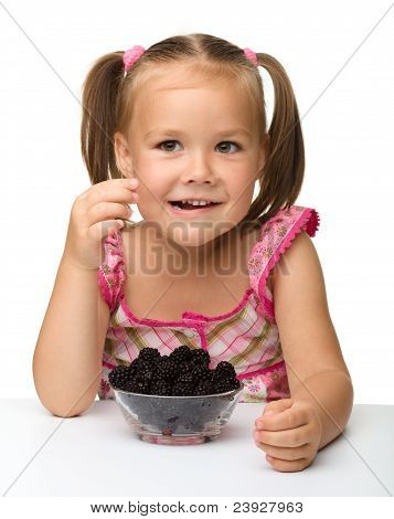 Cheerful Little Girl Is Eating Blackberry