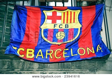 a FC Barcelona flag hanging on a balcony