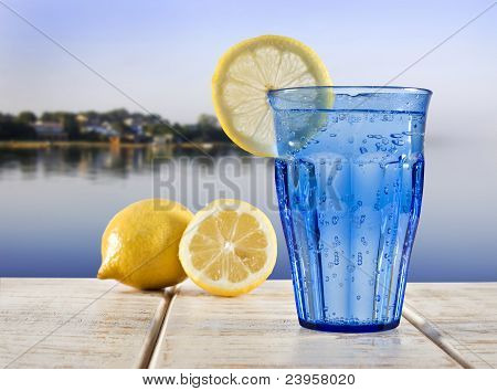 A Blue Glass With Sparkling Water And Lemon On A Wooden Deck Overlooking The Calm Water Of A Tropica