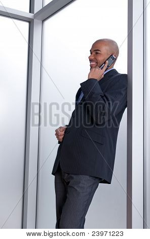 Businessman Leaning Against The Window, Talking On The Phone