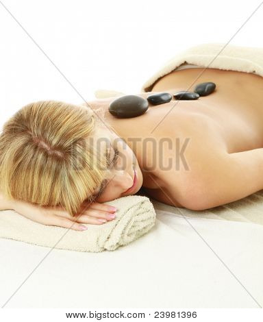 Relaxed young woman getting hot stone message at spa salon isolated on white