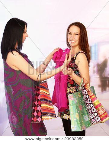 Two happy young women with shopping bags smiling isolated on blur background