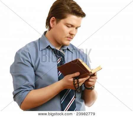 Young businessman with beads reading koran isolated