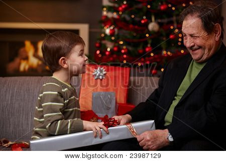 Small boy helping grandfather wrapping christmas gifts, smiling happily. ?