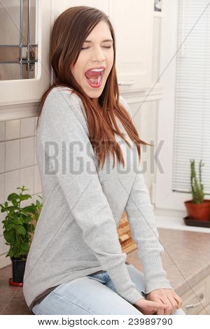 Young tired woman in kitchen yawing