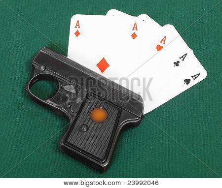 .22 cal semiautomatic pistol and four aces. Hazard metaphor.
