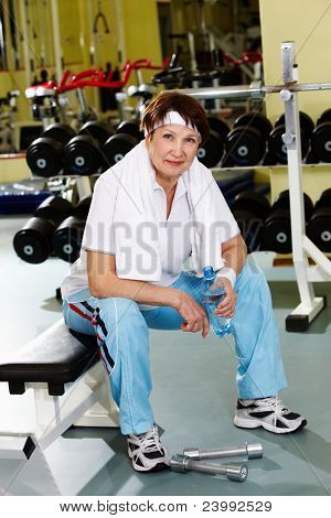 Portrait of senior woman in gym at break