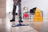 Low Section Of Male Janitor Cleaning Floor With Caution Wet Floor Sign In Office poster