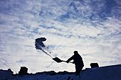 foto of snow shovel  - Removing snow from the roof in winter - JPG