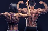 Couple Of Athletes Posing In Front Of The Camera Showing Their Athletic Backs And Hands On A Black B poster