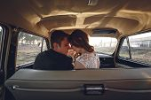 Young Wedding Couple Sitting Smiling Inside Retro Car. Just Married Embrace Is Hugging Inside Car. B poster