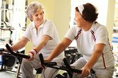 Two senior women training in health club