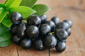 Bunch Of Fresh Seedless Red Grape On Wood Table. Black Grapes In Close Up View With Copy Space For B poster