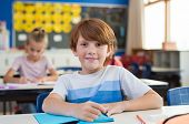 Portrait of happy child with freckles sitting at school desk in class room. Young boy smiling in cla poster