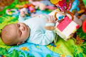 Cute Adorable Newborn Baby Playing On Colorful Toy Gym And Looking At The Camera. Closeup Of Peacefu poster