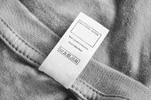 Care And Composition Clothes Label On Grey Cotton Background poster