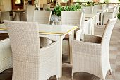 Empty Cafe With Rattan Wicker Armchairs And Tables On Summer Garden Terrace Outdoor, Free Space. Tab poster